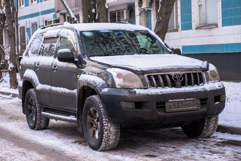 莫斯科,俄罗斯,11月,28日 2018年:在一条大城市街道上的被放弃的积雪的汽车丰田陆地巡洋舰 降雪的后果 免版税库存照片