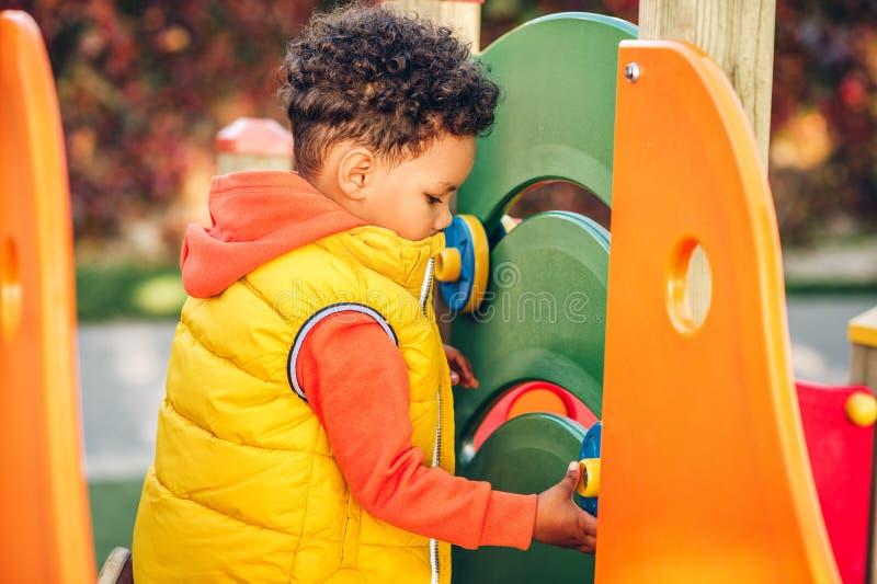 获得可爱的矮小的1-2岁小孩的男孩在操场的乐趣 免版税库存图片