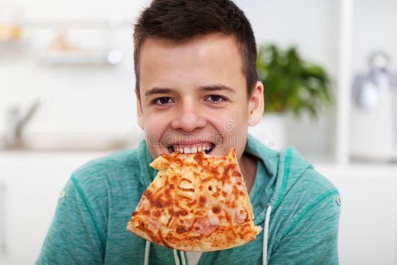 获得年轻的男孩吃一比萨-当切片的乐趣垂悬从他的牙 免版税库存图片