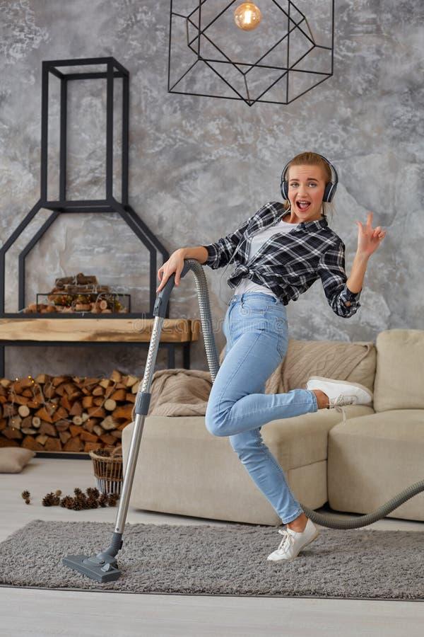 获得快乐的年轻女人20s全长画象听到音乐通过耳机和与吸尘器的乐趣 库存照片