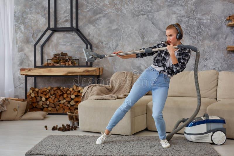 获得快乐的年轻女人20s全长画象听到音乐通过耳机和与吸尘器的乐趣 库存图片
