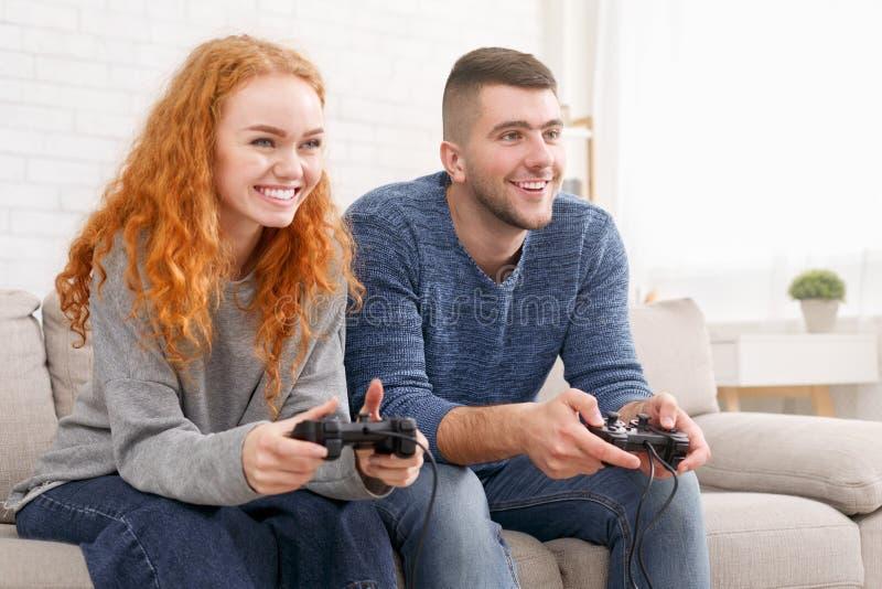 获得激动的夫妇一起打电子游戏和乐趣 库存图片