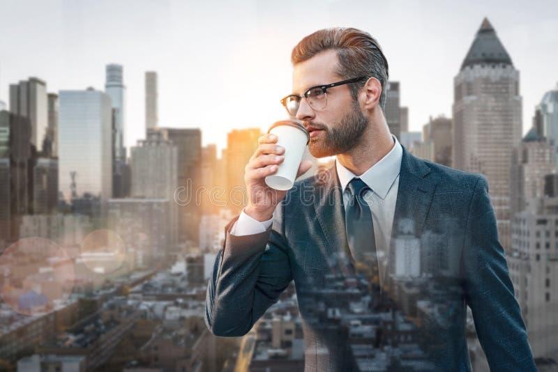 背景中断咖啡新月形面包杯子甜点 喝热的咖啡和考虑事务的时髦的商人,当站立户外与都市风景时 图库摄影