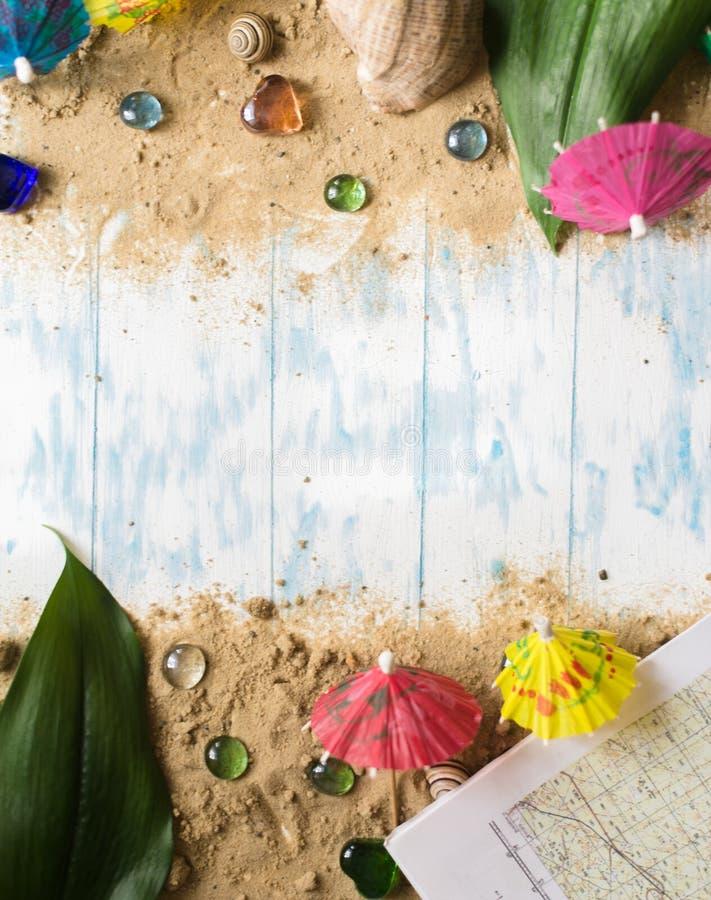背景概念框架沙子贝壳夏天 鸡尾酒的伞在木背景的沙子与小卵石 库存照片