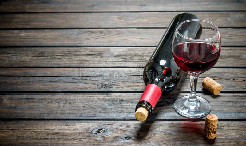 背景玻璃红葡萄酒 在一个瓶的红葡萄酒有玻璃的 库存照片