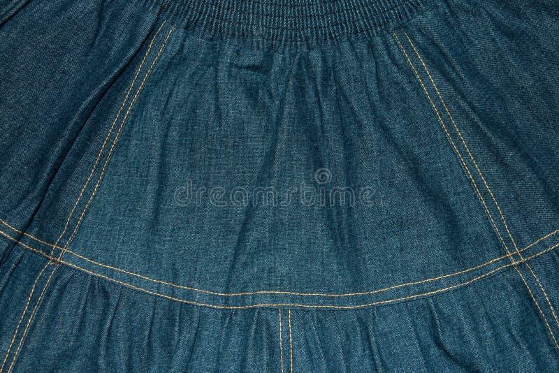 背景,一条减速火箭的牛仔布裙子的纹理 库存图片