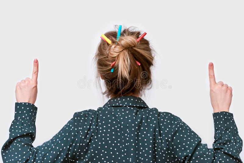 背面图年轻女人画象的演播室关闭有五颜六色的铅笔的在头发,指向与食指 库存图片