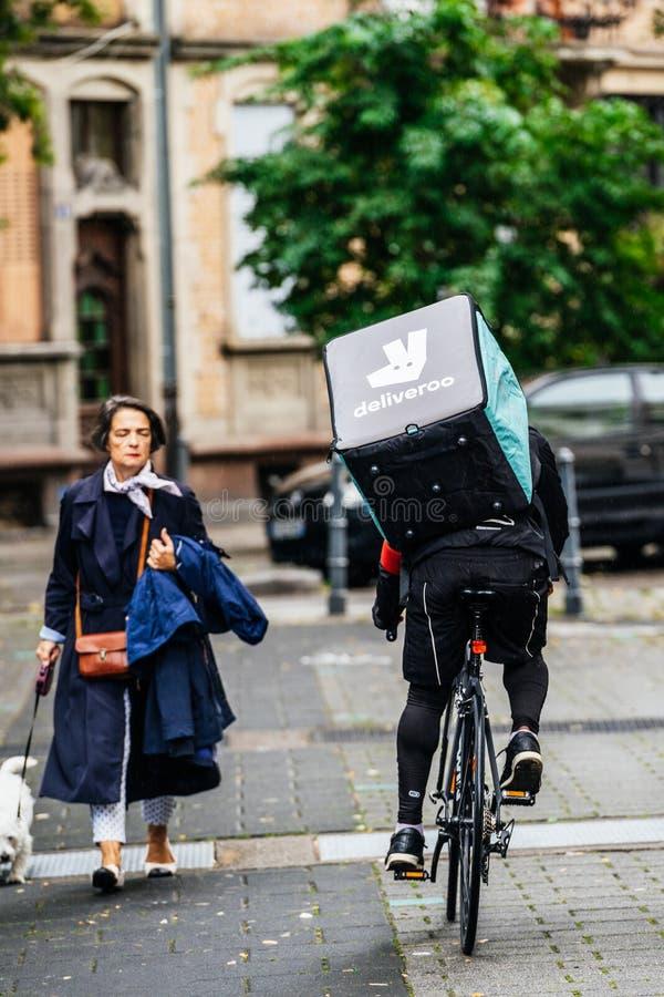 背面图Deliveroo骑自行车者快速循环在法国街道上 库存照片