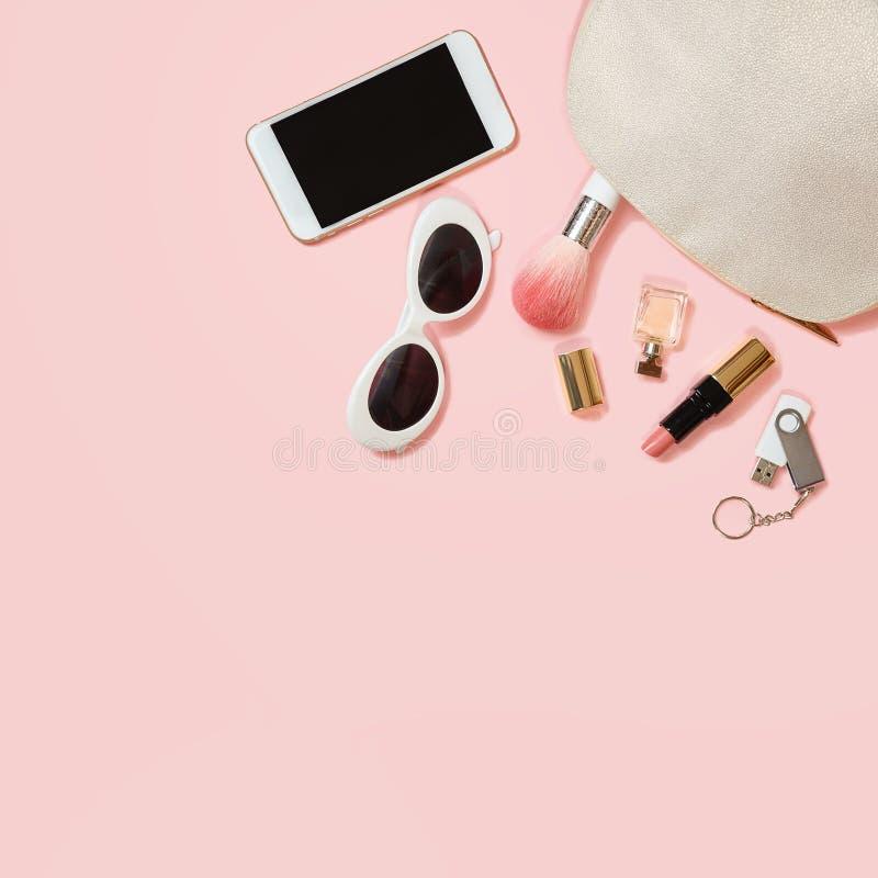 舱内甲板在粉红彩笔背景的被放置的女性辅助部件化妆用品太阳镜手机耳机一刹那推进构成 华伦泰` s 免版税库存图片