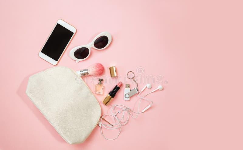 舱内甲板在粉红彩笔背景的被放置的女性辅助部件化妆用品太阳镜手机耳机一刹那推进构成 华伦泰` s 免版税图库摄影