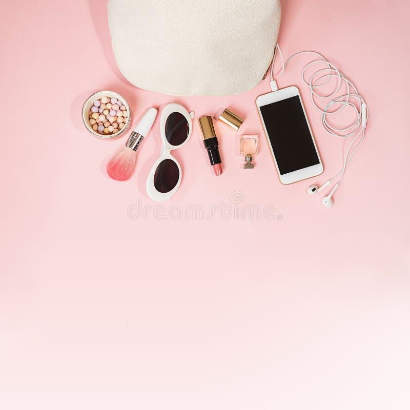 舱内甲板在粉红彩笔背景的被放置的女性辅助部件化妆用品太阳镜手机耳机构成 情人节3月8日 免版税图库摄影