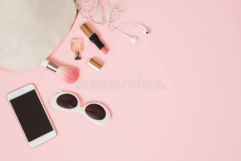 舱内甲板在粉红彩笔背景的被放置的女性辅助部件化妆用品太阳镜手机耳机构成 情人节3月8日 库存照片