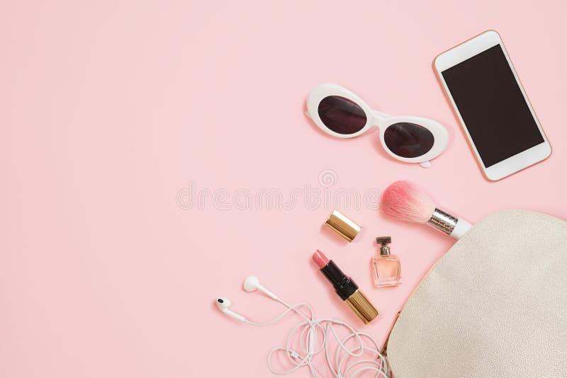 舱内甲板在粉红彩笔背景的被放置的女性辅助部件化妆用品太阳镜手机耳机构成 情人节3月8日 免版税库存照片
