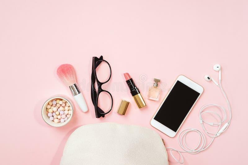 舱内甲板在粉红彩笔背景的被放置的女性辅助部件化妆用品玻璃手机耳机构成 情人节3月8日 库存照片