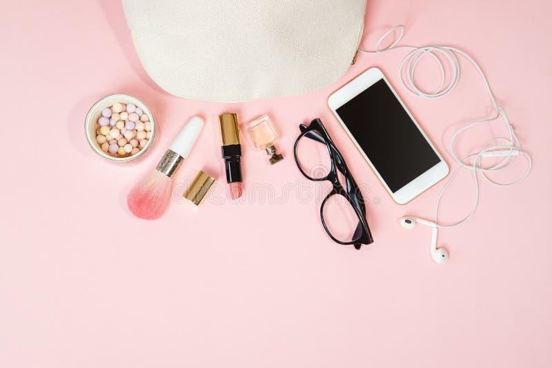 舱内甲板在粉红彩笔背景的被放置的女性辅助部件化妆用品玻璃手机耳机构成 情人节3月8日 库存图片
