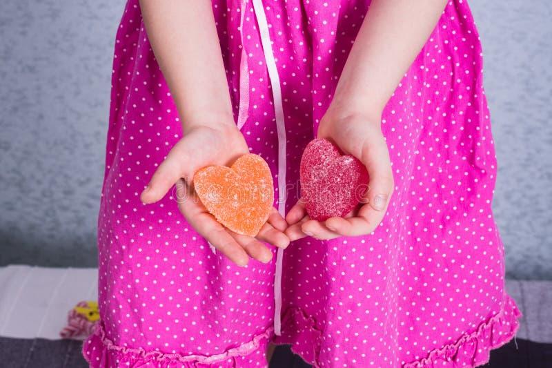 舒展在她的棕榈的女孩两橘子果酱心脏 儿童保护天概念 情人节,爱天 免版税库存图片
