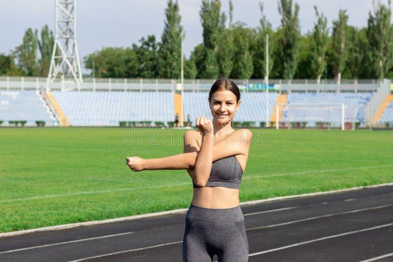 舒展和做准备在体育场体育和健身概念的跑的轨道的年轻女运动员 库存照片