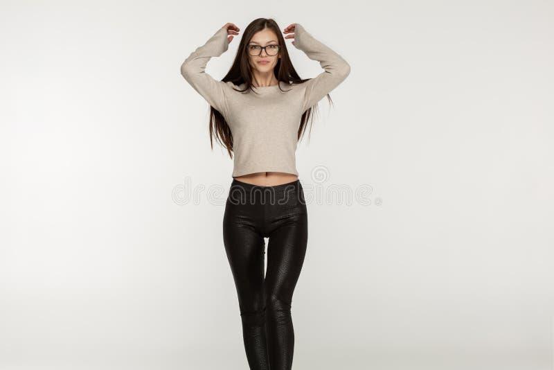 舒展胳膊的玻璃和黑绑腿的美丽的深色的年轻女人  免版税库存图片