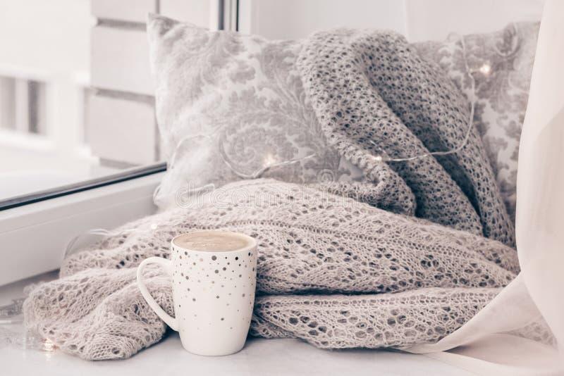 舒适针织品和一个枕头有一杯咖啡的在白色大理石窗台反对白色窗口背景 免版税库存照片