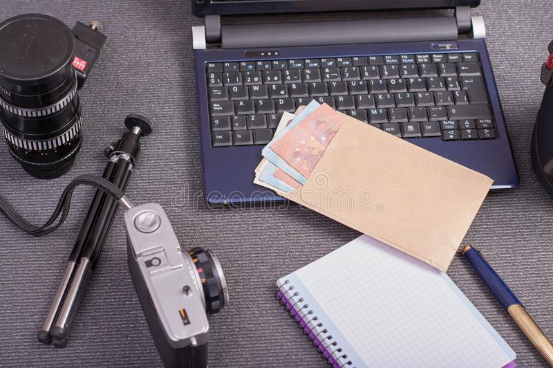 葡萄酒在膝上型计算机旁边的照片照相机片剂一个智能手机和一个信封与金钱在欧元 图库摄影