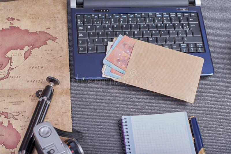 葡萄酒在膝上型计算机旁边的照片照相机片剂一个智能手机和一个信封与金钱在欧元 库存图片