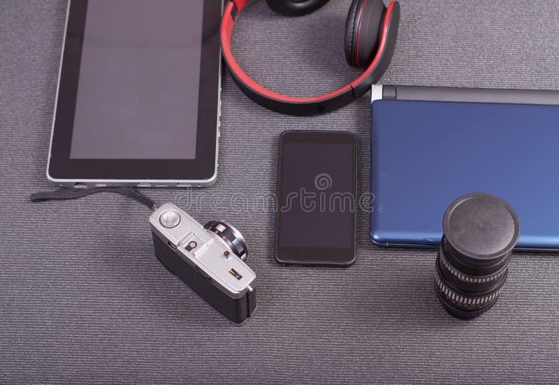 葡萄酒在膝上型计算机旁边的照片照相机片剂和智能手机 免版税库存照片