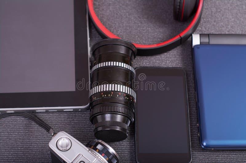 葡萄酒在膝上型计算机旁边的照片照相机片剂和智能手机 库存照片