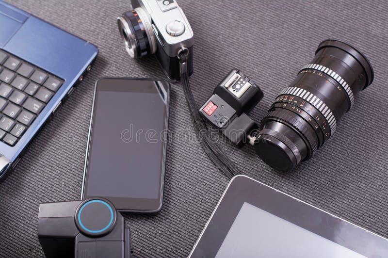 葡萄酒在膝上型计算机旁边的照片照相机片剂和智能手机 免版税库存图片