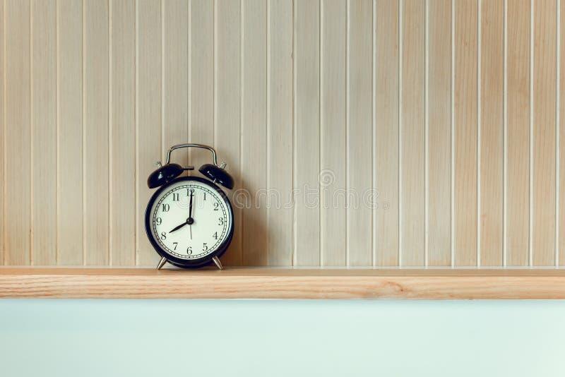 葡萄酒减速火箭在床头板架子、内部卧室和装饰设计的闹钟 黑定时器时钟是布局反对  免版税图库摄影