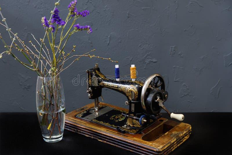 葡萄酒缝纫机有蓝色花的一个花瓶 图库摄影