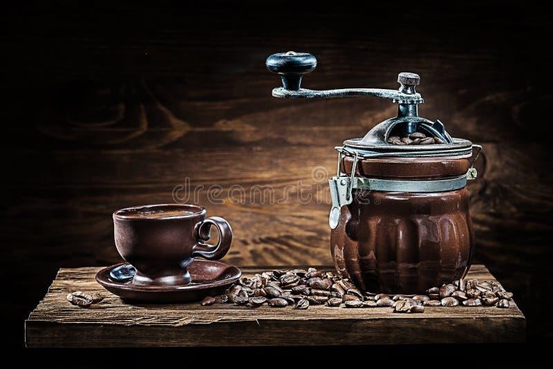 葡萄酒黏土咖啡碾和杯子用豆在木委员会 免版税库存图片
