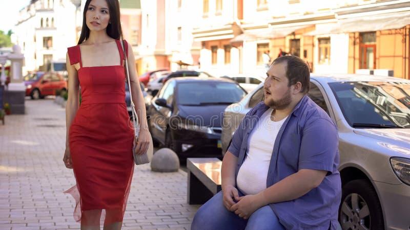 肥胖男性看的美丽的端庄的妇女,生活方式区别,刺激 免版税库存照片
