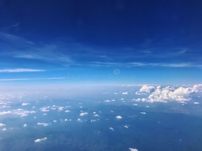 蓝天和从飞机窗口的云顶视图鸟瞰图  免版税库存图片