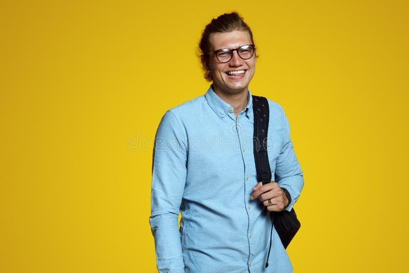 蓝色拿着背包和微笑对在黄色背景的照相机的衬衣和镜片的英俊的年轻人 免版税库存照片