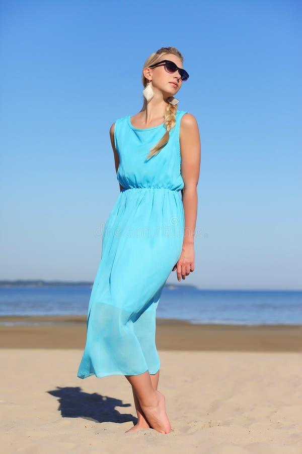 蓝色礼服和太阳镜的女孩在天空背景  图库摄影