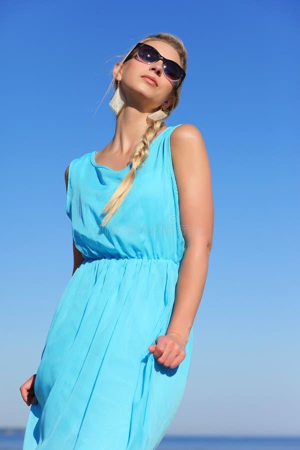 蓝色礼服和太阳镜的女孩在天空背景  免版税库存照片