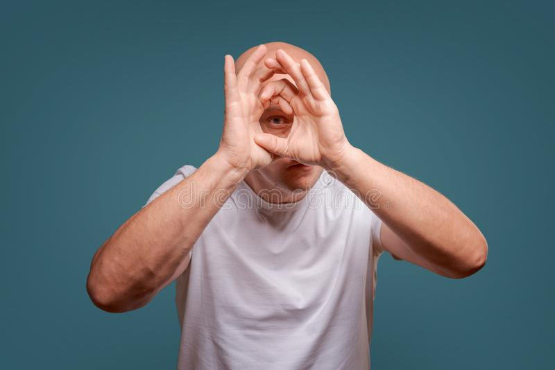 蓝色背景的一个人在握在他的眼睛附近的手象望远镜窥视 库存图片