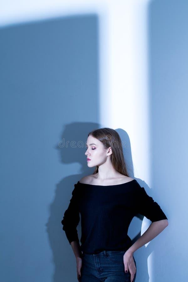 蓝色阴影在背景和在黑毛线衣的美好的白肤金发的模型 库存图片