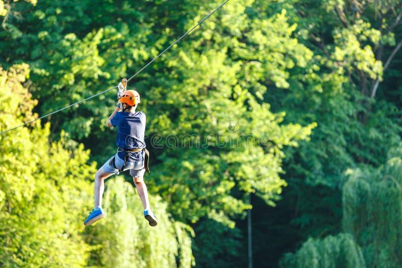 蓝色T恤杉的快乐的逗人喜爱的年轻男孩和橙色盔甲在冒险绳索公园晴朗的夏日 活跃生活方式,体育 免版税库存照片