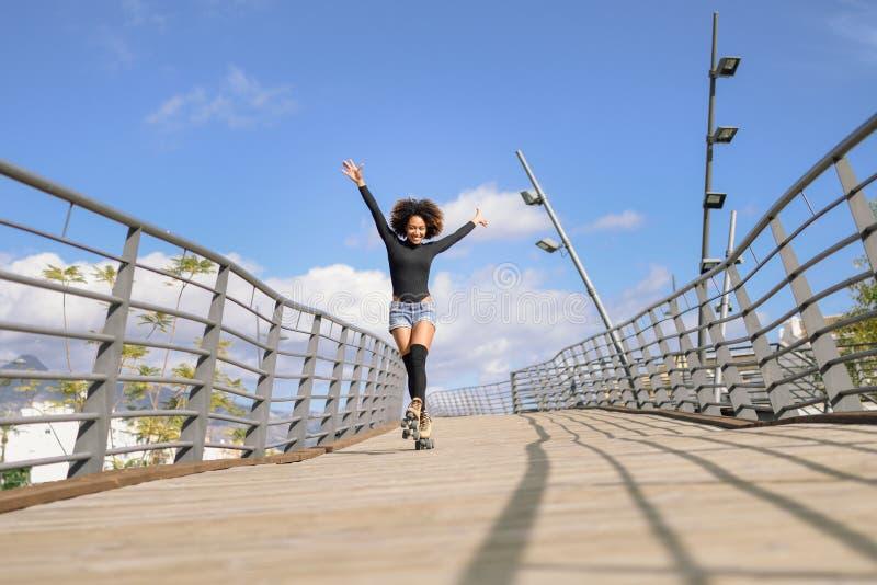 蓬松卷发乘坐户外在都市桥梁的溜冰鞋的发型妇女 库存图片