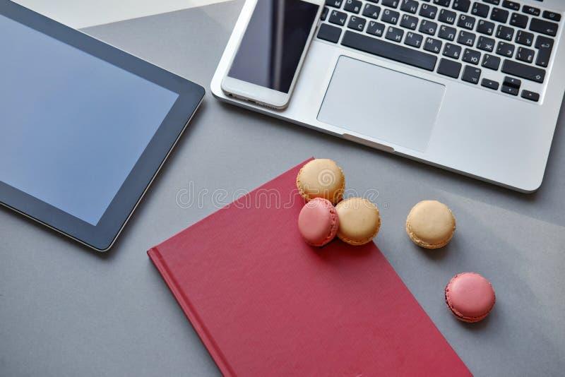 膝上型计算机、片剂、智能手机、笔记本和五颜六色的法国macaron在桌上 工作,午餐,办公室 库存图片