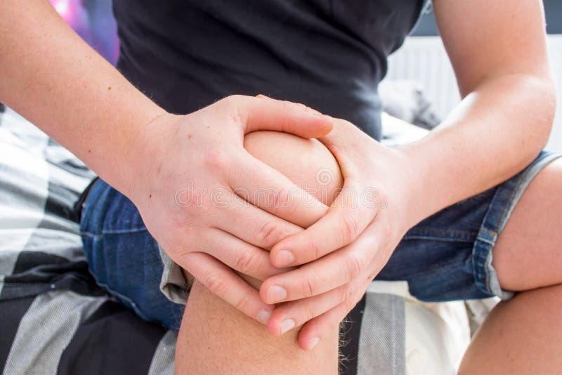 膝盖痛苦概念照片 白种人男性藏品在膝盖后的两只手,刺穿深刻锐痛,当坐边缘如此时 图库摄影