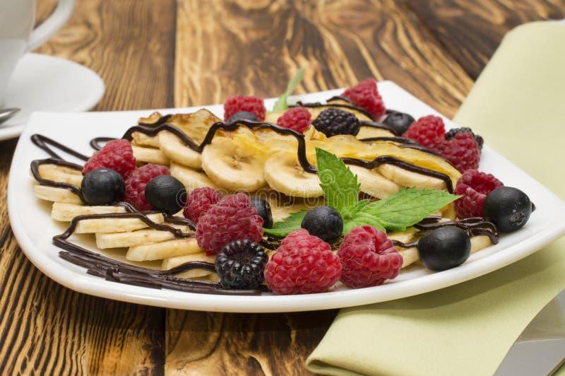 自创绉纱服务与巧克力奶油,香蕉,新鲜的蓝莓,在木背景的莓,薄煎饼 库存图片