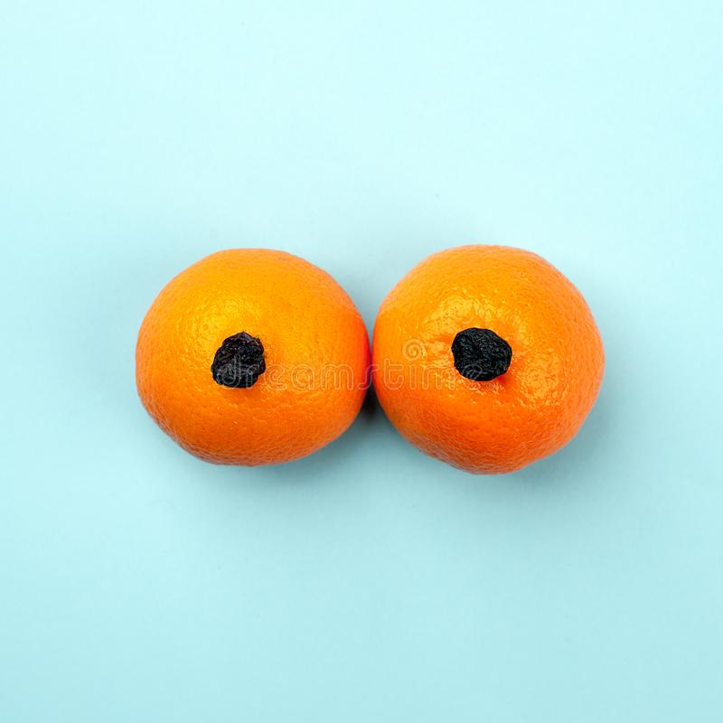 自然有机异乎寻常的柑桔和干葡萄作为妇女的乳房,胸象与拷贝空间 免版税库存图片