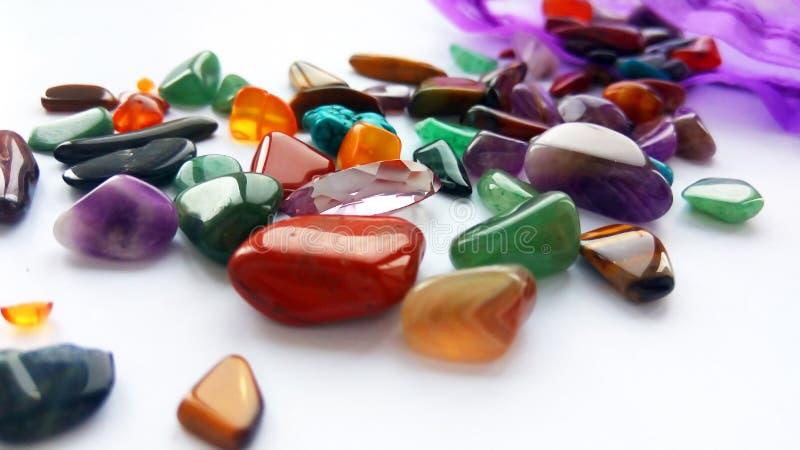 自然明亮的色的半珍贵的宝石和宝石与一个袋子在白色背景 库存图片