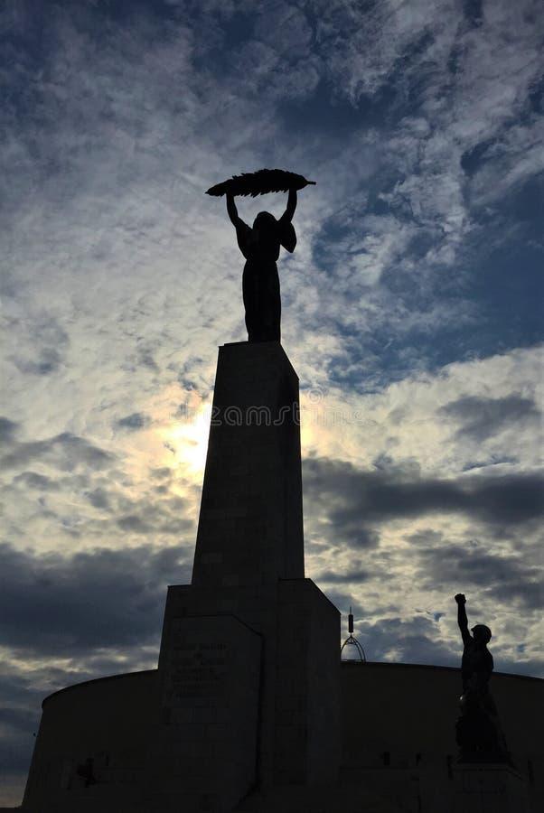 自由女神像-拿着棕榈叶状体的古铜色妇女 免版税库存图片