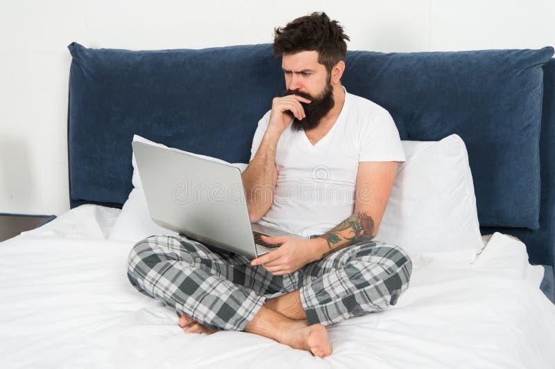 自由职业者的工作 逗留在床上和继续工作 自由职业者的好处 人冲浪的互联网或在网上工作 有胡子的行家 免版税库存照片