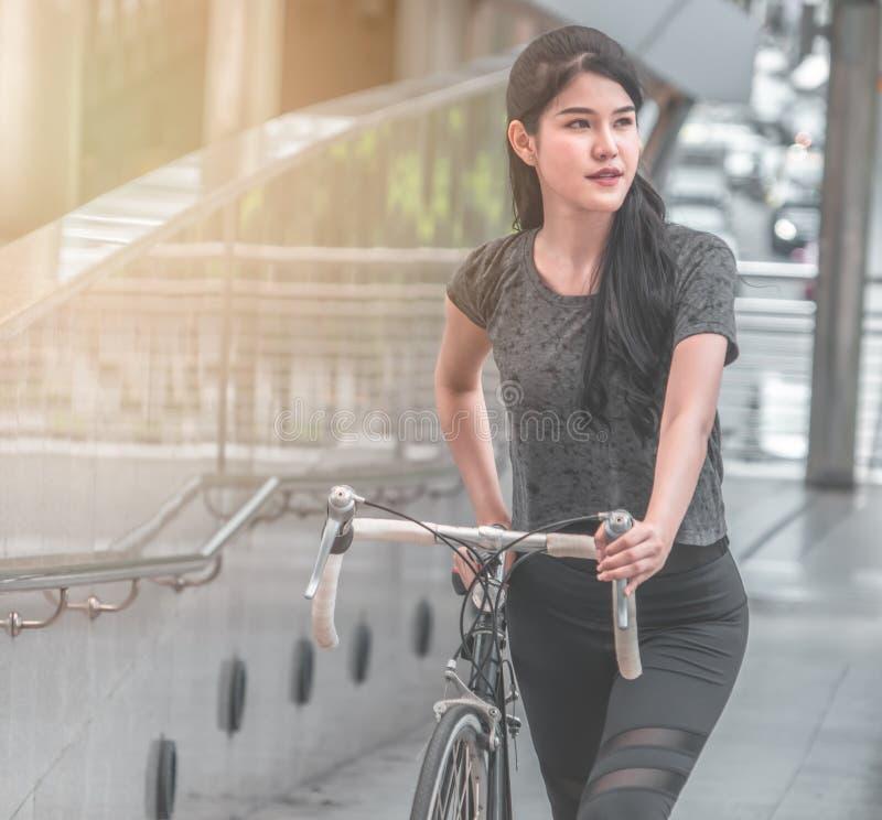 自行车的女孩在城市与太阳火光的早晨 图库摄影