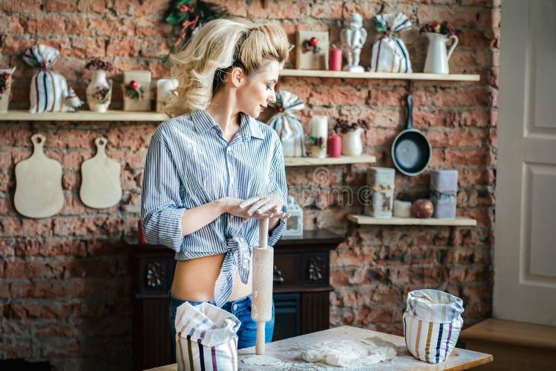 色情性感的年轻女人的金发碧眼的女人在厨房里准备面团 主妇有袋子的面粉和有滚针的在厨房里 免版税图库摄影
