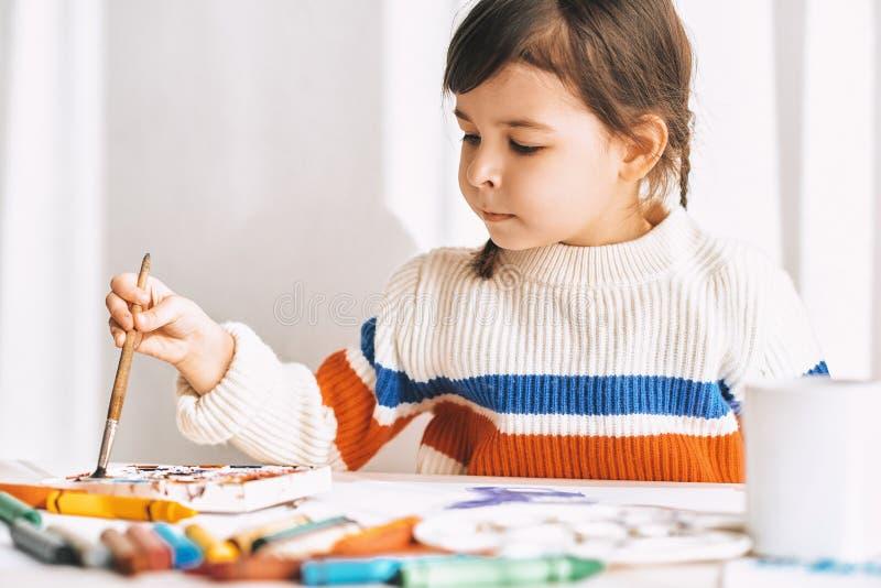 艺术性的女孩绘画和在家画与铅笔和水彩在白色书桌上 免版税库存照片